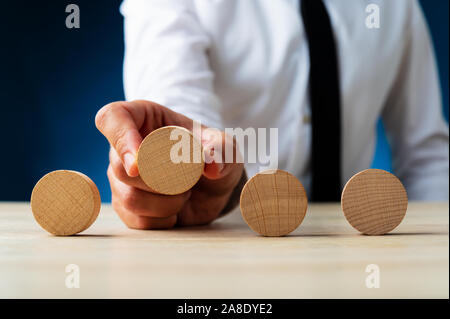 Businessman placing four blank wooden cut circles in a line in front of him in a conceptual image of advertisement and promotion. - Stock Photo