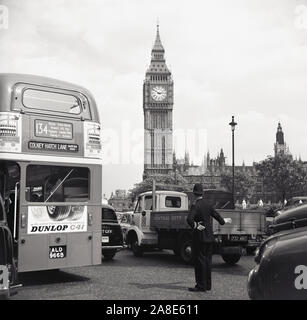 1960s, historical, British policeman directing traffic at Parliament Square, London, England, with the Clock Tower seen in the distance. A 134 routemaster bus going to Colney Hatch Lane can be seen as well as other cars and trucks of the era. - Stock Photo