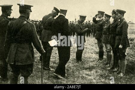 """King George V decorates British personnel, Belgium, First World War, 1914-1918, (c1920). 'The King's Visit to Belgium: presenting decorations to heroes of the Royal Naval Air Service'. George V (1865-1936) at the Western Front. From """"The Great World War: A History"""", Volume VI, edited by Frank A Mumby. [The Gresham Publishing Company Ltd, London, c1920] - Stock Photo"""