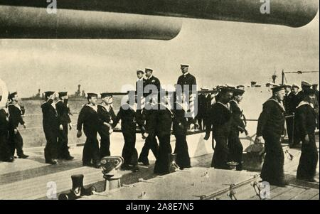 """'The King's Visit to the Grand Fleet', First World War, June 1917, (c1920). '...bluejackets [sailors of the Royal Navy] marching past His Majesty [King George V] on board one of the battleships' at Scapa Flow off the north coast of Scotland. George's son Prince Albert (later King George VI), was serving on board HMS 'Malaya' at the time. From """"The Great World War: A History"""", Volume VII, edited by Frank A Mumby. [The Gresham Publishing Company Ltd, London, c1920] - Stock Photo"""