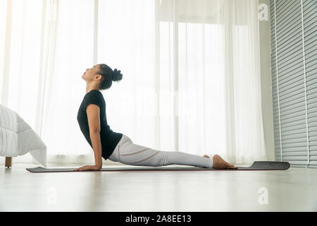 Middle aged women doing yoga in bedroom at the morning, adho mukha svanasana pose. Concept of exercise and relaxation in the morning. - Stock Photo