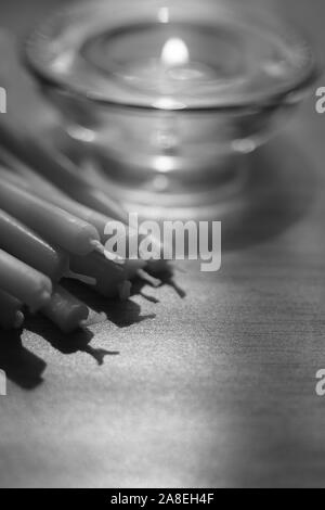 heap of new long candles and one low candle burns in a glass round candlestick, macro, bw - Stock Photo