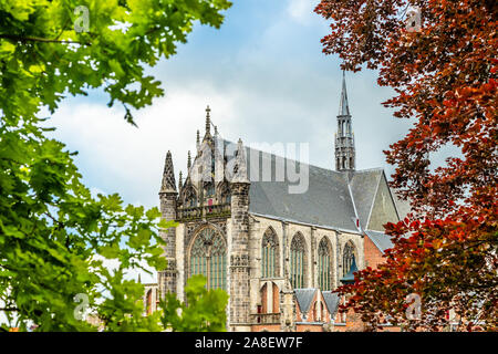 Hooglandse Kerk, old protestant gothic style cathedral, partly hidden in the foliage, Leiden, The Netherlands - Stock Photo