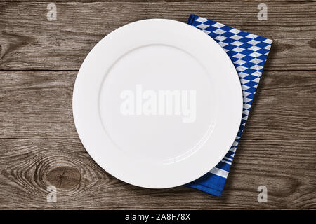 Empty white plate with bavarian napkin on a wooden table, top view. Food background - Stock Photo