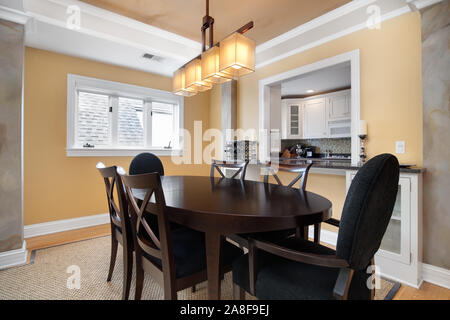 A small dining room in a condo that is overlooked by a window from the kitchen. A dark table and chairs is centered under a modern light fixture. - Stock Photo