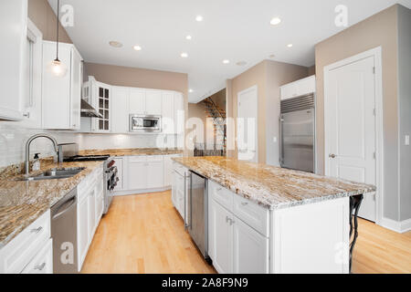 A large white kitchen in a luxurious home with wood floors, stainless steel appliances, granite, and white cabinets. - Stock Photo