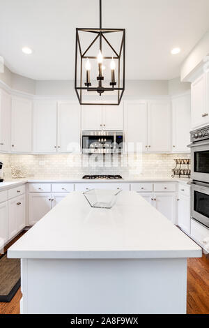 A bright kitchen with white cabinets, white granite counter tops, stainless steel appliances and light fixture hanging over the island. - Stock Photo