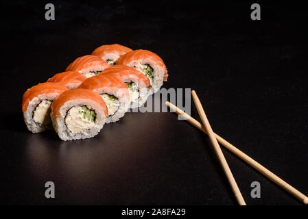 Various kinds of sushi served on a dark background. Roll with salmon, avocado, cucumber. Sushi menu. Japanese food.