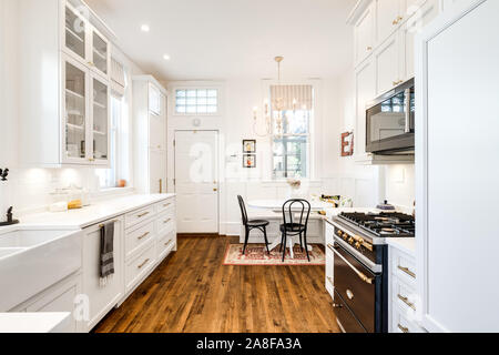 A white kitchen with a small dining room area in the corner and hardwood floors throughout. - Stock Photo