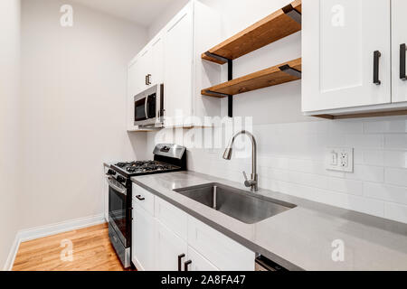 A small kitchen in a Chicago condo with white cabinets and GE stainless steel appliances. Wood shelves are hanging over the sink with subway tiles. - Stock Photo