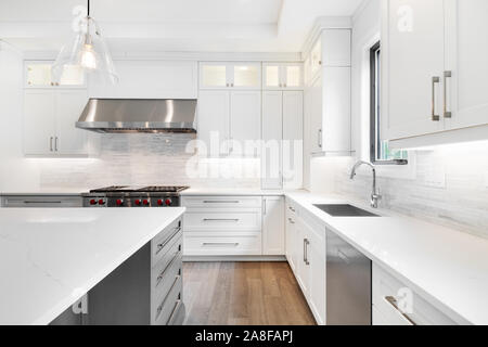 A luxurious modern kitchen with stainless steel Wolf appliances surrounded by white cabinets, beautiful granite, and hardwood floors. - Stock Photo