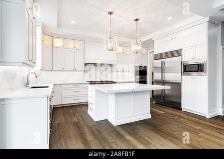 A luxurious modern white kitchen with stainless steel Wolf, Subzero, and Whirlpool appliances. - Stock Photo