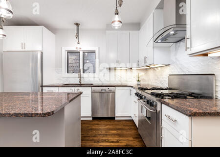 An elegant, modern kitchen featuring grey and white speckled granite, stainless steel appliances, white cabinets and stainless steel appliances. - Stock Photo
