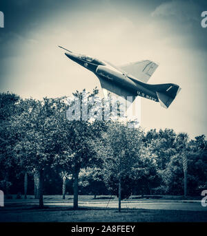 A low flying vintage US Navy Blue Angels airplane banking over treetops in the USA - Stock Photo