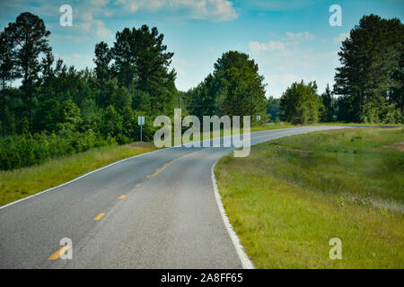 A curving  empty asphalt highway leading through pine trees in rural Southern Mississippi, USA - Stock Photo