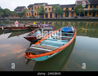 Close up of a colorful wooden fishing boat with painted eye moored on the Thu Bon River in Hoi An Vietnam with gold stucco riverfront buildings in the - Stock Photo