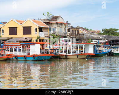 Colorful passenger boats docked along Thu Bon riverfront in Hoi An, Vietnam. - Stock Photo