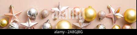 Extra wide Christmas border with golden and silver Xmas balls and pink stars on ivory background. Flat lay, top view, overhead. Christmas frame design - Stock Photo