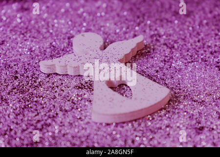 Wooden figurine of a little angel on a shiny pink background. Christmas holiday concept. - Stock Photo