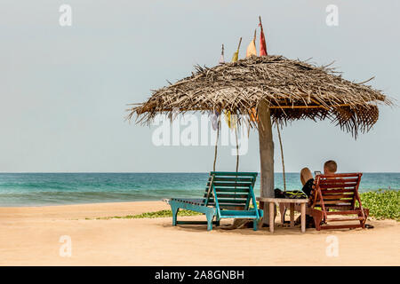 A guy is relaxing at Bentota beach in Sri Lanka. - Stock Photo