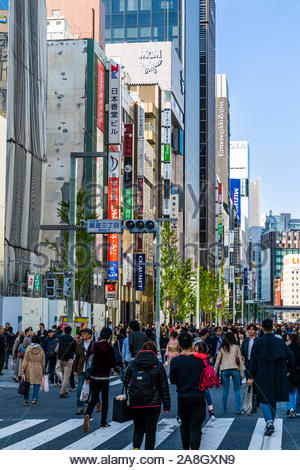 Street view of Chuo Dori street, the main shopping street of the Ginza in Tokyo, on a weekend when it becomes a pedestrian precinct. Busy and crowded. - Stock Photo