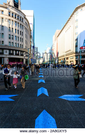 Ginza, Tokyo's top shopping district. Street view, Chuo Dori on weekend when its a pedestrian precinct. Crossroads with Wako and Mitsukoshi buildings. - Stock Photo
