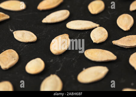 Roasted and salted pumpkin seeds on black board, shallow depth of field photo - Stock Photo