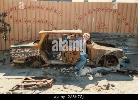 Michael Scott/Alamy Live News - Berlin, Germany April 1990 - A Holiday picture taken in East in April 1990 just months after the Berlin Wall fell in 1989 of a burnt out Trabant with graffiti 'Future of Communism' . - Stock Photo