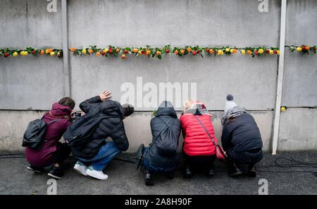 Berlin, Germany. 09th Nov, 2019. After the commemoration ceremony of the Berlin Wall Foundation on Bernauer Strasse, passers-by look through the cracks in the Wall to the former death strip. At the commemoration ceremony, Federal President Steinmeier and Chancellor Merkel, together with the heads of state of Poland, Slovakia, the Czech Republic and Hungary, recalled the opening of the Berlin Wall 30 years ago. Credit: Kay Nietfeld/dpa/Alamy Live News - Stock Photo