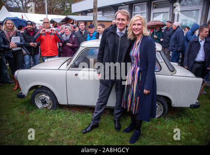 09 November 2019, Schleswig-Holstein, Lübeck-Schlutup: Manuela Schwesig (SPD), Prime Minister of Mecklenburg-Vorpommern, and Daniel Günther (CDU, r), Prime Minister of Schleswig-Holstein, are standing in the border museum near the former Schlutup border crossing at the ceremony commemorating the fall of the Berlin Wall 30 years ago in front of a Trabant. Schlutup was at the time the northernmost border crossing via which GDR citizens flocked to the West after the surprising opening of the border. Photo: Jens Büttner/dpa-Zentralbild/dpa - Stock Photo