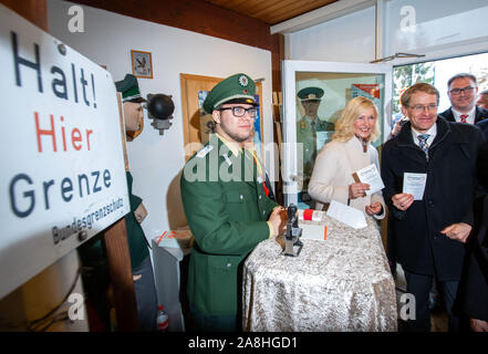 09 November 2019, Schleswig-Holstein, Lübeck-Schlutup: Manuela Schwesig (SPD), Prime Minister of Mecklenburg-Vorpommern, and Daniel Günther (CDU, r), Prime Minister of Schleswig-Holstein, receive the exit stamp to the GDR from a Federal Border Guard in the Border Museum near the former Schlutup border crossing at the celebration commemorating the fall of the Berlin Wall 30 years ago. Schlutup was at the time the northernmost border crossing via which GDR citizens flocked to the West after the surprising opening of the border. Photo: Jens Büttner/dpa-Zentralbild/dpa - Stock Photo