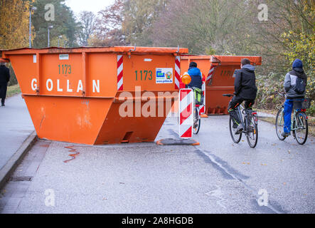 09 November 2019, Schleswig-Holstein, Lübeck-Schlutup: Visitors ride their bicycles through a lock made of mill containers which protects the access road to the festival mile at the border museum near the former Schlutup border crossing from possible attacks. A celebration on the grounds of the border museum commemorates the fall of the Wall 30 years ago. Schlutup was at the time the northernmost border crossing via which GDR citizens flocked to the West after the surprising opening of the border. Photo: Jens Büttner/dpa-Zentralbild/dpa - Stock Photo