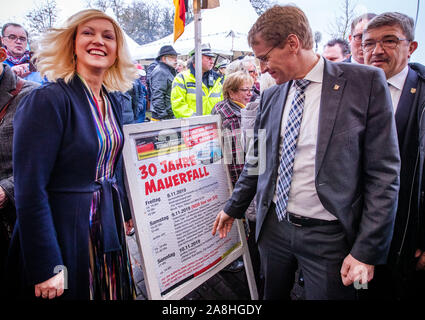 09 November 2019, Schleswig-Holstein, Lübeck-Schlutup: Manuela Schwesig (SPD), Prime Minister of Mecklenburg-Vorpommern, and Daniel Günther (CDU, r), Prime Minister of Schleswig-Holstein, are standing on the event poster at the border museum near the former Schlutup border crossing, celebrating the fall of the Berlin Wall 30 years ago. Schlutup was at the time the northernmost border crossing via which GDR citizens flocked to the West after the surprising opening of the border. Photo: Jens Büttner/dpa-Zentralbild/dpa - Stock Photo