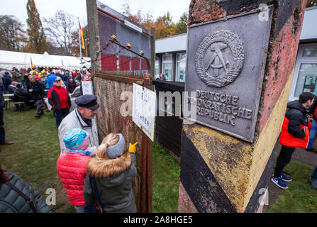 09 November 2019, Schleswig-Holstein, Lübeck-Schlutup: Visitors stand at the original wire fence of the border security installations and the border column with the national coat of arms of the German Democratic Republic in the border museum near the former Schlutup border crossing. A celebration here commemorates the fall of the Wall 30 years ago. Schlutup was at the time the northernmost border crossing via which GDR citizens flocked to the West after the surprising opening of the border. Photo: Jens Büttner/dpa-Zentralbild/dpa - Stock Photo