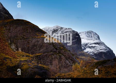Season change from autumn to winter in Scottish highlands.Clear sky above snow capped mountain peaks and autumn colors in valley below.Beautiful scene. - Stock Photo