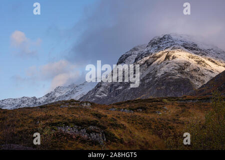 Dramatic sky over snow capped mountain range lit by rising sun and autumn colours in valley below.Majestic landscape of Glencoe in Scottish highlands. - Stock Photo