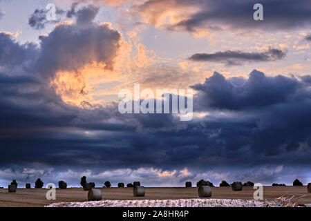 Storm clouds gathering on the horizon over bales of hay - Stock Photo