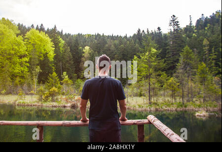 Man alone standing and looking on the desolate lake in forest. Concept of travel, psychology, mindfulness.