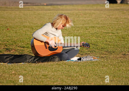 A young woman tunes her guitar while sitting in a public park along the Deschutes River in Bend, Oregon