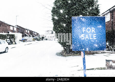 Snow covered cars, recycling bins, roads and houses at night in Longton, Stoke on Trent,  winter, black ice and cold weather, poor driving conditions, - Stock Photo