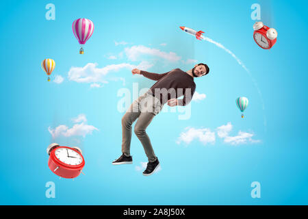 Young man and two alarm clocks floating in blue sky with rocket and hot air balloons in background. - Stock Photo