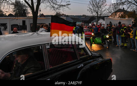 09 November 2019, Bavaria, Mödlareuth: As part of the celebrations to mark the 30th anniversary of the fall of the Berlin Wall, a Trabant column travels through a specially erected 'Wall Opening'. The commemoration ceremony is under the motto 'The Trabants are coming.'. Photo: Nicolas Armer/dpa - Stock Photo