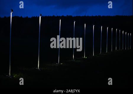 09 November 2019, Bavaria, Mödlareuth: As part of the celebrations to mark the 30th anniversary of the fall of the Berlin Wall, a light installation recalls the course of the former border wall. The commemoration ceremony is under the motto 'The Trabants are coming.'. Photo: Nicolas Armer/dpa - Stock Photo