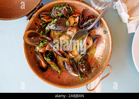 a restaurant copper serving bowl full of mussels and clams cooked in white wine sauce with garlic and parsley a traditional Portuguese dish called Ame - Stock Photo