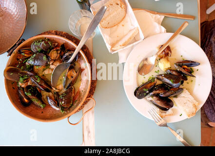 a restaurant table with a copper serving bowl and white plate full of mussels and clams, garlic and parsley a traditional Portuguese dish called Ameij - Stock Photo