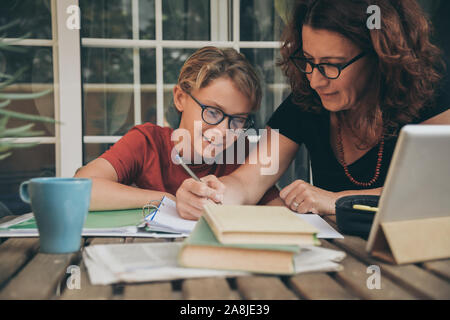 Young student doing homework at home with school books, newspaper and digital pad helped by his mother. Mum writing on the copybook teaching his son.