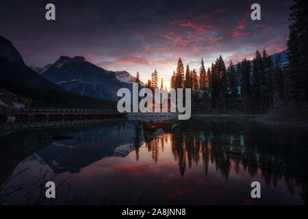 Sunrise at Emerald Lake, a jewel in the Rockies. Mirror reflection, colorful clouds, a cabin and the trees. Small house at the end of a bridge. Yoho. - Stock Photo