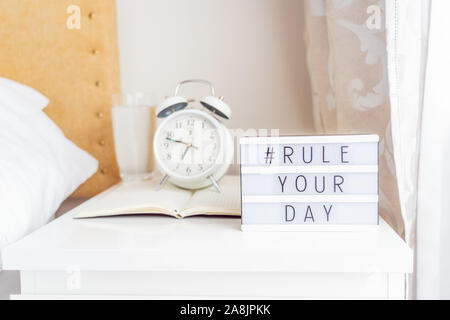 Inspiration Motivational Life Quotes hashtag Rule your day message on lightened box with alarm clock and open notebook on the bedside table in the sun - Stock Photo