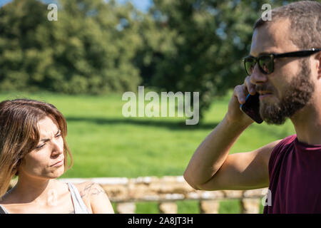 Stock photo of a girl looking with serious expression to a boy with sunglasses that talks to the mobile phone - Stock Photo