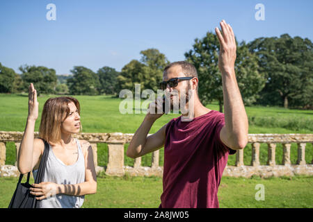Stock photo of a girl arguing with raised hand with a boy who talks to the mobile in a garden - Stock Photo